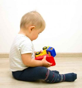 Lonely little boy   playing with plastic toy truck on a floor