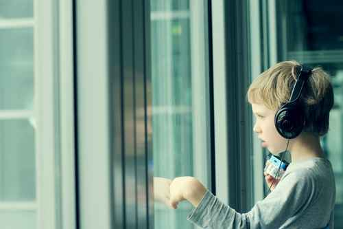 boy with headphones looking out the window at the airport